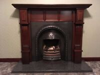 Fireplace with ornate cast iron surround and marble hearth, grate and basket.