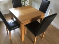 Solid oak table and 4 leather chairs.