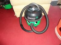 green and black henry hoover with pipe in good working order