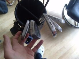 9 golf clubs various sizes with a bag