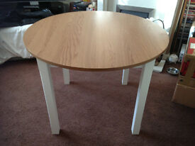 Brand new wood effect round table with four used chairs and cushions,..