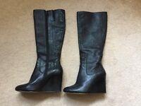 Nine West knee length, high wedge heel black boots.
