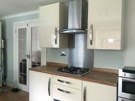 Cream gloss kitchen units with neff double oven, cooker hood and indesit dishwasher