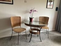 Beautiful round glass dining table with two chairs / wicker