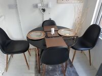 Black glass an copper dining table and chairs good condition