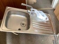 As new kitchen sink with plug and mixer tap