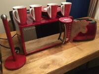 Red microwave, toaster, kitchen roll holder, pendulum clock, cow chopping board and 4 cups.
