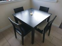Black wooden table and four chairs for dining room