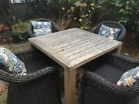 Gloster brand teak table and four rattan chairs w cushions and pillows