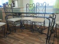 Ornate metal and glass dining table and 6 cream chairs