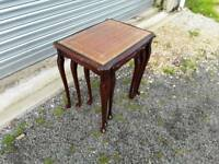Nest of three tables, leather inset with glass