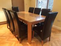 Full stave solid oak dinning table and eight black leather chairs, chunky wood