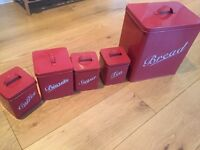 Set of red metal storage containers and bread bin