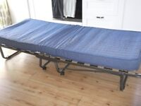 Fold-up spare bed for sale. Comfortable mattress on a sturdy metal frame.