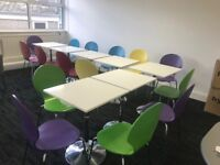 Numerous dining tables and multicoloured chairs