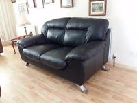 Very modern and clean 2 seater black leather sofa in excellent condition