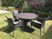 Four armed, stacking Rattan style garden chairs with 107cm diameter round glass topped table.