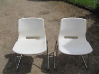 2 white steel framed plastic occasional chairs for in the house or on the patio in the garden.