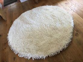 Circular Ivory Shenkin pile rug.