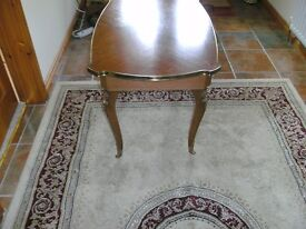 Occasional light mahogany table with ornamental legs. Has a swivel top, under-storage with cutlery