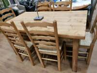 Solid farmhouse table with small drawer with 6 ladderbacked chairs