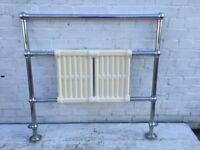 Chrome towel rail with cast iron radiator