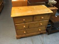 SMALL PANELLED BACK AND DRAWERS PINE CHEST OF FOUR DRAWERS
