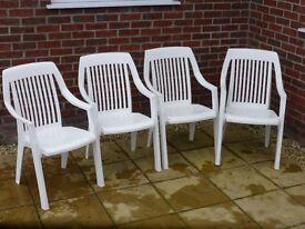 Four white plastic garden chairs.
