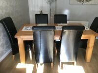 Solid wooden table and six faux leather chairs