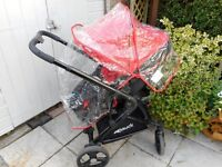red and black rear and forward facing pram push chair with rain cover