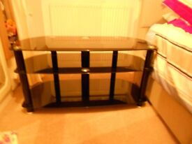 TELEVISION STAND BLACK GLASS AS NEW CONDITION . NO MARKS OR SCRATCHES.