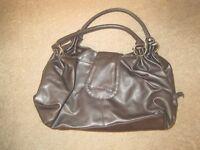 Medium sized dark brown handbag as seen in photo. Plain on back.