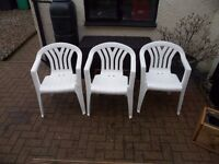 Six White Plastic Chairs Three Metal Stools And Small Blue Table