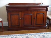 A solid wood 3 door sideboard with cutlery drawer finished in unmarked polished mahogany