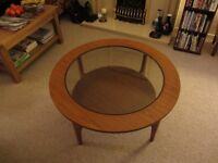 Wooden circular coffee table with glass top.