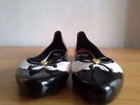 MEL BY MELISSA BLACK AND WHITE FLAT SANDALS WITH A SLIM BOW.