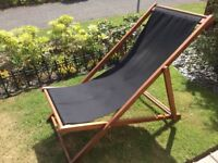excellent condition 2x wooden sunloungers with black canvas lie on