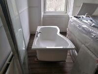 Curved bath with screen, panel and taps