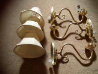 3 gold wall lights with cream lamp shades