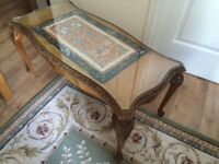 Antique coffee table with a glass top for a living room