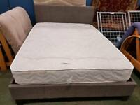 Grey fabric covered double bed frame with mattress