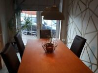 Next Oak dining room table and 6 dark brown faux leather chairs.