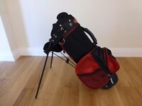Red Ogre junior golf bag with stand, raincover, 5 wood, 6 iron, sandwedge and putter.