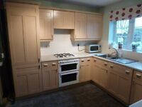 Modren light oak shaker style kitchen units and dresser including integrated/built under appliances.
