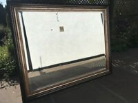 Large mirror with copper/gold effect.