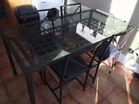 Glass top dining table with 4 X chairs wicker seats.