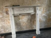 Timber fire surround. With mouldings. Painted white. Small shelf.