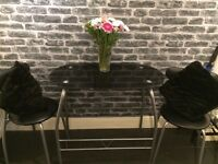 Black glass space saving table and two chairs very good condition £25 Ono