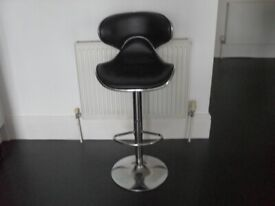 Black gas lift bar stool in used condition has slight tear on back of chair.