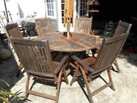 Good quality garden teak table with 6 chairs and parasol
